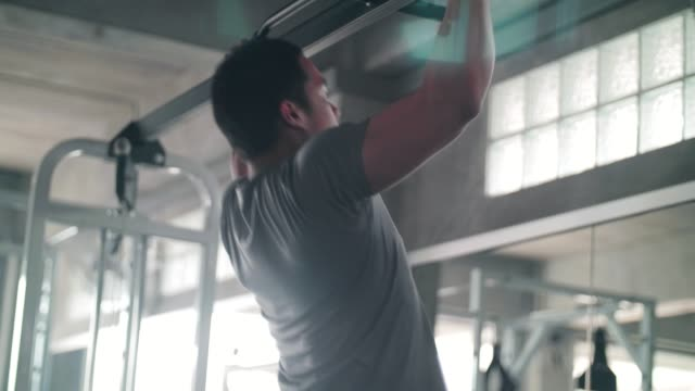 determined man doing chin-ups at gym - banchi scuola video stock e b–roll