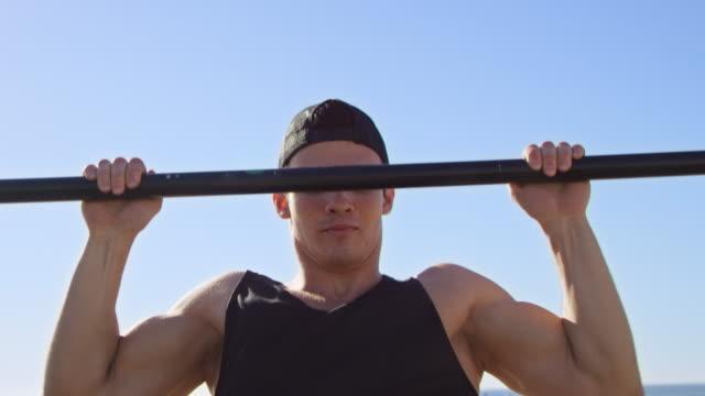 vídeos de stock e filmes b-roll de determined man doing chin-ups on jungle gym - 20 24 anos