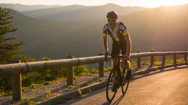 determined road cyclist cycling uphill - ciclismo su strada video stock e b–roll