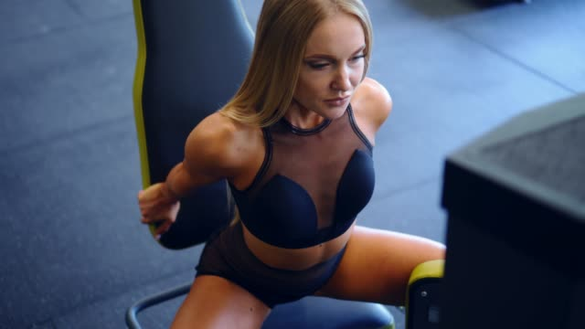 Determined woman exercising at hip abductor machine video