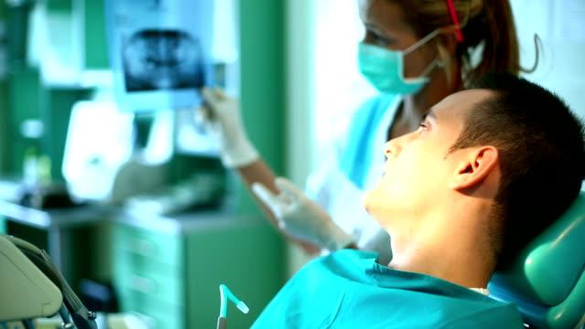 Detnist muestra imagen radiográfica a un paciente. - vídeo