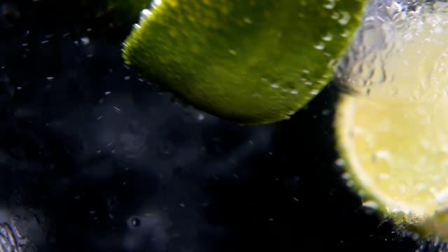 detoks ya da susuzluk kavramı. sağlıklı, diyet beslenme. soğuk limonata, limon içecek. siyah arka plan - kokteyl i̇çki stok videoları ve detay görüntü çekimi