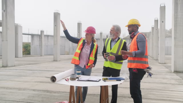 vídeos de stock e filmes b-roll de developers and foreman going over plans at construction site - arquiteto