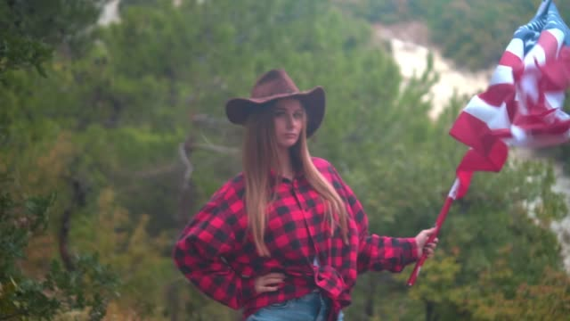 A developing American flag in the hand of a beautiful girl in a cowboy hat, a red shirt and blue jeans