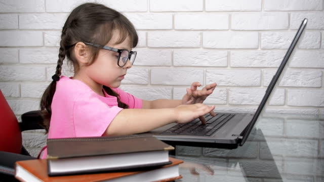 Device addiction. Internet addiction. Device addiction. Internet addiction. A child at the computer. Girl with bad eyesight have a device addiction. Mother tries to take notebook away but she fails. pigtails stock videos & royalty-free footage