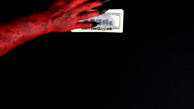 djävulens hand spelas med en hög med pengar. 50 fps - dirty money bildbanksvideor och videomaterial från bakom kulisserna