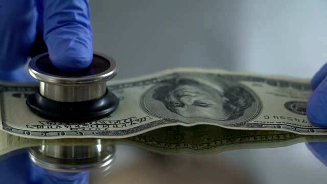 diagnostik der dollar mit stethoskop, finanziellen markt überwachungskonzept - inflation stock-videos und b-roll-filmmaterial