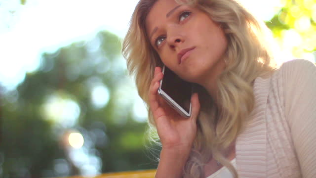 Dialing and calling phone young blond in park daytime video