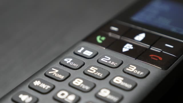 Dialing keyboard of modern cordless phone hi-tech design in office 4K Dialing keyboard of modern cordless phone hi-tech design in office 4K 2160p 30fps UltraHD footage - Portable fixed telephone line device on the table 4K 3840X2160 UHD video landline phone stock videos & royalty-free footage