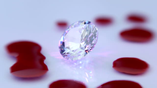 Diamond and falling drops of blood. Closeup Diamond  and falling drops of blood transfused in colorful rays of light. The camera moves around double refraction stock videos & royalty-free footage