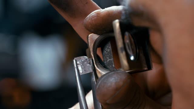 un diamante viene lucidato da un operaio specializzato nel centro di lavorazione dei diamanti - brillante video stock e b–roll