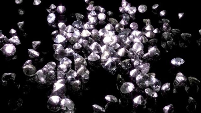 diamonds cascade onto reflective surface - bling bling stok videoları ve detay görüntü çekimi