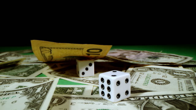 SLO MO Dices rolling over bunch of dollars
