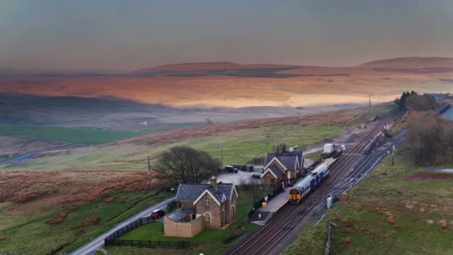 stockvideo's en b-roll-footage met diesel passagierstrein aankomst in ribblehead, north yorkshire - drone shot - groot brittannië
