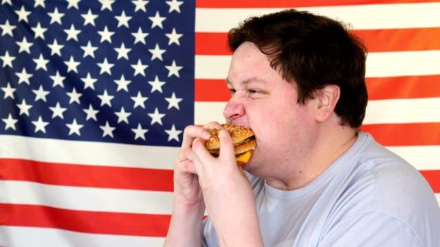 diet failure of fat man eating fast food hamburger. american national food - cheeseburger filmów i materiałów b-roll