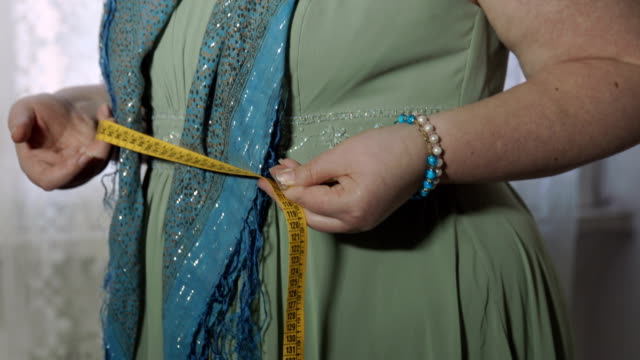 diet problems: fat woman with a measurement tape in her hands video