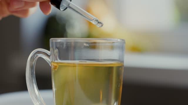 пищевые добавки и витамины - добавление капель в чашку чая с капельницы - vitamin d стоковые видео и кадры b-roll
