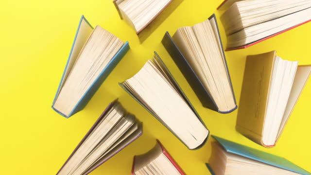 vídeos y material grabado en eventos de stock de diferentes libros aparecen en el fondo amarillo - detener movimiento - libro