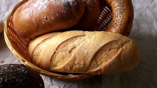 Different bread in the basket on table close-up. Different bread in the basket on table close-up, slow motion. bun bread stock videos & royalty-free footage