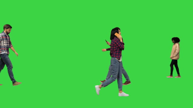 Different casual people walking by on a Green Screen, Chroma Key