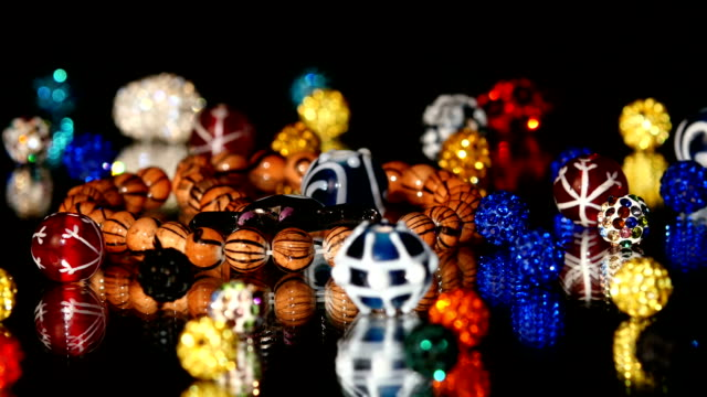 Different colorful beads on black background, cam moves to the left, rotation