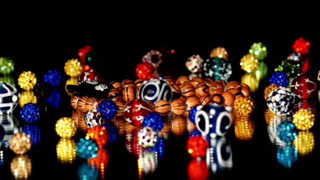 Different colorful beads on black background, rotation
