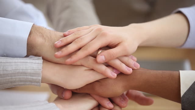 Different ethnicity people hands stacked together close up view