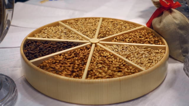 different grains are beautifully laid out in a wooden tray and glass vases - orzo video stock e b–roll
