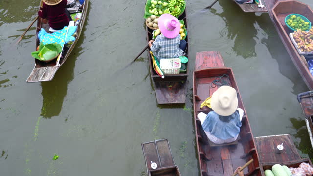 Different kinds of foods, fruits and vegetables sold on boats in the canal at floating market.