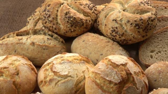 木製のテーブルに新鮮なパンの種類。茶色の背景にパンの品揃え。 - 木目点の映像素材/bロール