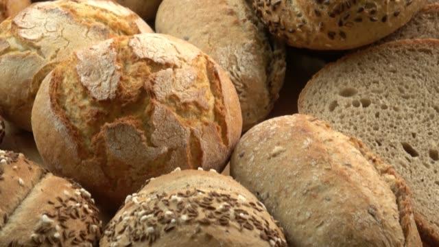 木製のテーブルに新鮮なパンの種類。茶色の背景にパンの品揃えを分離。 - 木目点の映像素材/bロール