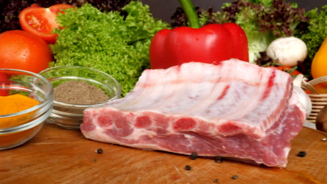 Different kinds of meat lie on wooden boards on the background of vegetables of lettuce leaves, special, slow passage of video from the side.