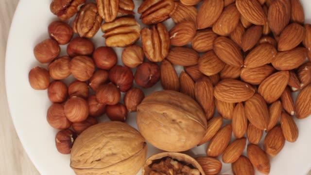 vídeos de stock e filmes b-roll de different nuts on a white plate in a kitchen - amendoas