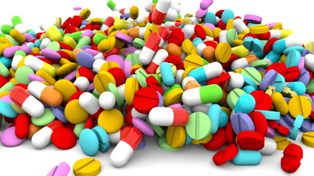 Different pills fall on a white surface 4k