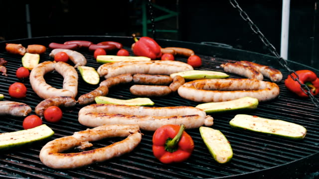 Different sausages are roasted on huge grill with vegetables. Food Festival video
