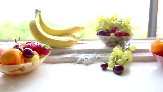 vídeos de stock e filmes b-roll de diferentes frutas de verão em um peitoril de janela - saladeira