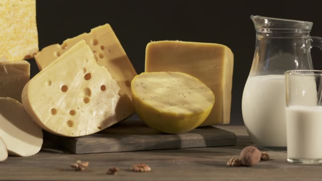 Different types of cheeses with milk jug on wooden table video