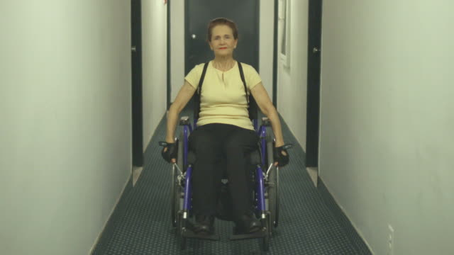 Differently Abled Senior Woman using Wheelchair in Apartment Hallway video