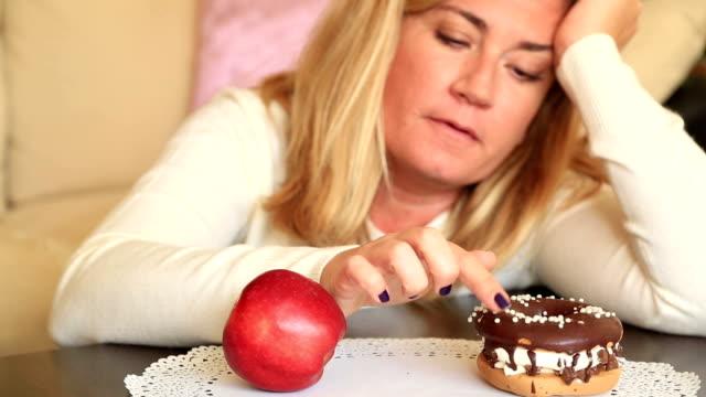 迷惑か健康食品、ダイエットの概念の間の困難な選択 - 体への関心点の映像素材/bロール