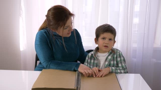 trudna edukacja dla niewidomych dzieci, młody nauczyciel uczy niedowidzących chłopców czytać książki brajlowskie z symbolami czcionki siedzi przy stole w pokoju - store filmów i materiałów b-roll