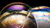 istock Diffraction and interference of light through soap bubbles . Slow motion macro video 1128441893