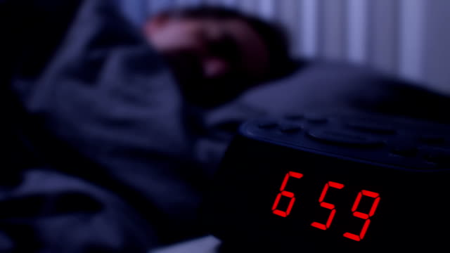 Video Digital alarm clock, man waking up at 7am.