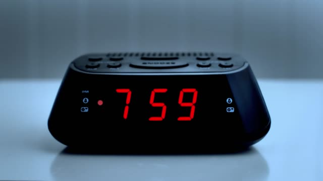 Digital alarm clock, time from 7.59 to 8.00.