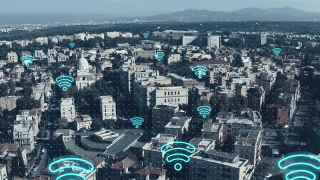 Digital city of future concept. Aerial view of European cityscape with wireless communication networks WI-FI neon symbols, IoT Internet of Things, Big Data web connections in all buildings and houses video