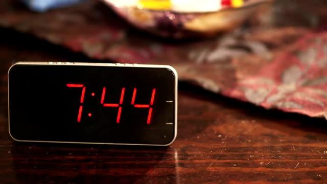 digital clock placed on wooden table when the time's passing - alarm clock bildbanksvideor och videomaterial från bakom kulisserna