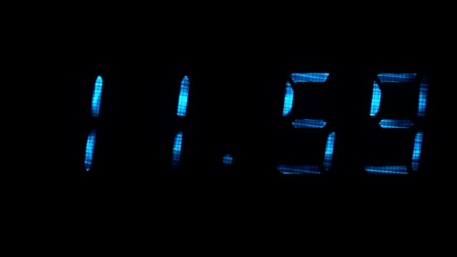 Digital clock shows the time of 11 hours 59 minutes to 12 hours 00 minutes video