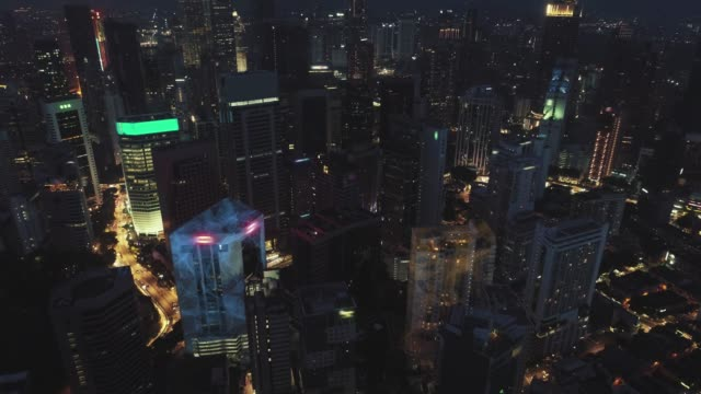 Digital network connection lines of Kuala Lumpur. Financial district and business centers in smart urban city in Asia. Skyscraper and high-rise buildings at night.