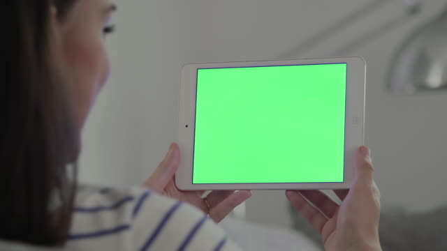 Digital tablet chromakey, woman close up on a sofa.