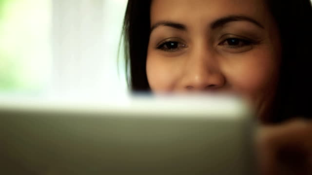 Digital tablet, close. SE Asian woman. video