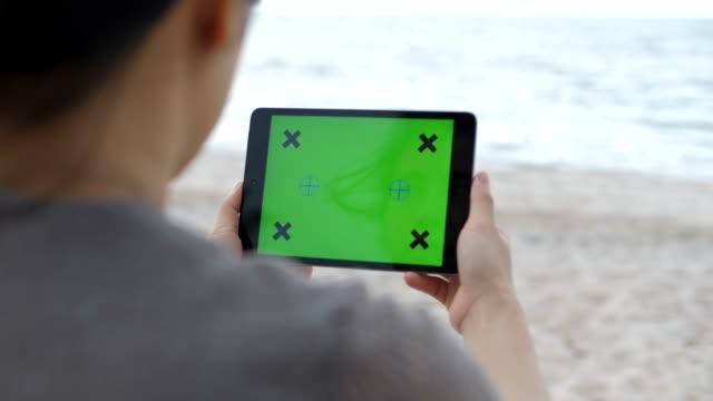 digital tablet on the beach - surfować po internecie filmów i materiałów b-roll